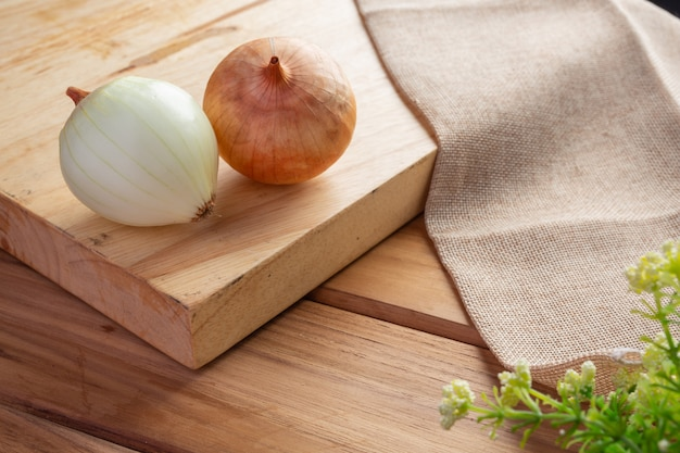 Two onions on a light brown wood cutting board. Free Photo
