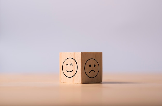 Two opposite side of emotion of happy and sad which print screen on wooden cubic. customer experience survey and satisfaction feedback concept. Premium Photo
