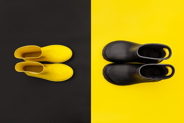 Two pairs of gumboots - yellow female and black male - standing opposite to each other on the inverse backgrounds. Premium Photo