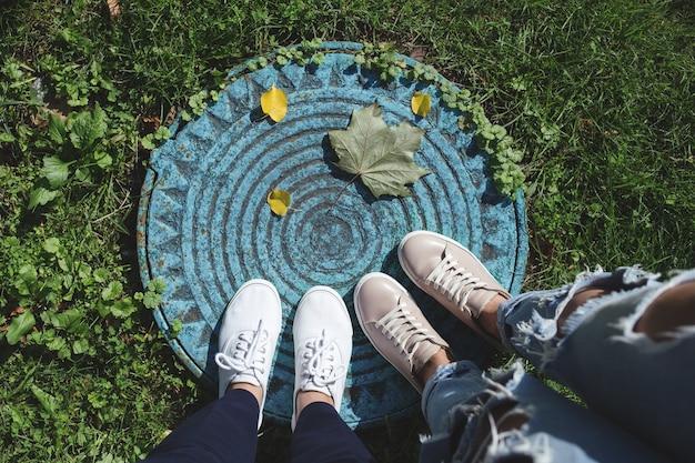 Две пары женских ног и опавшие листья на люке Premium Фотографии