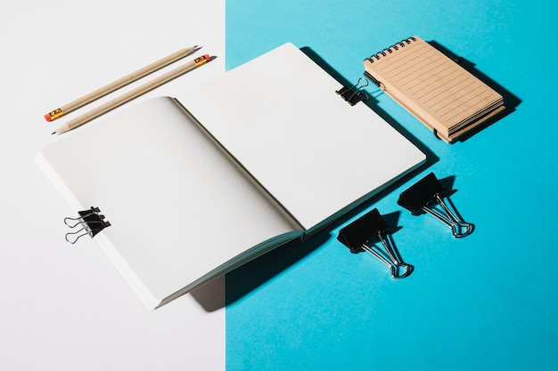 Two pencils; open notebook attach with bulldog clip and spiral notepad Free Photo