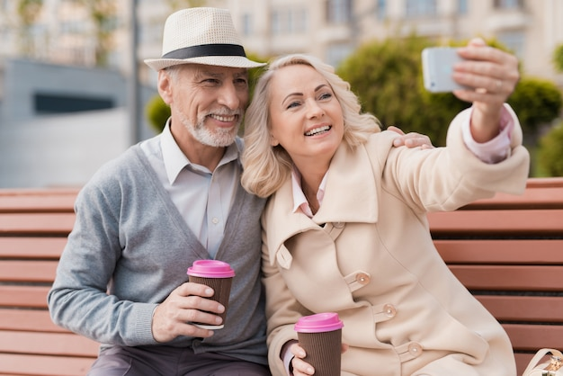 Two pensioners are sitting on bench with a glass of coffee. Premium Photo