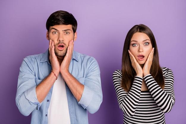 Двое людей пара держатся за щеки слушают негативные ужасные ужасные новости носить стильную повседневную одежду изолированные пастельный фиолетовый цвет стена Premium Фотографии