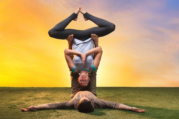 Two people doing yoga exercises | Free Photo