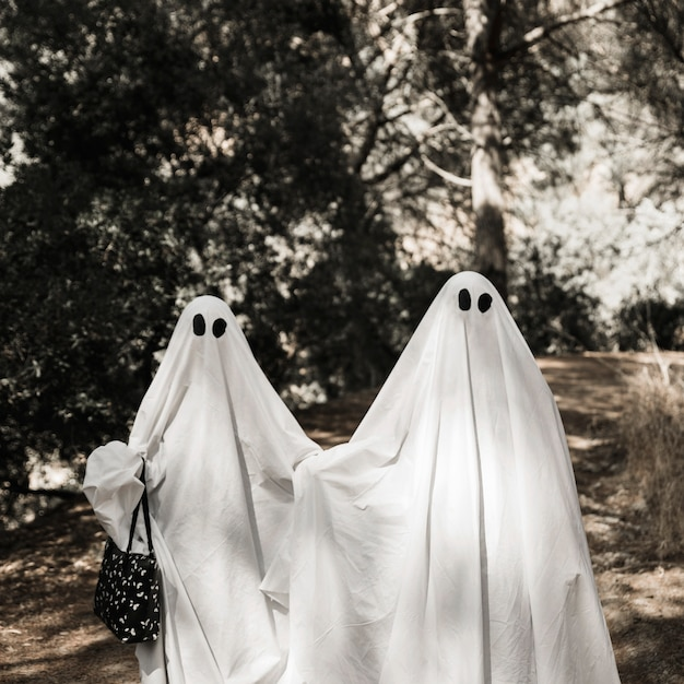 Two people in ghost costumes walking in forest Free Photo