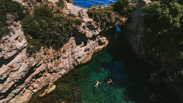 Two people in green bay in capri island italy inside cave view Premium Photo