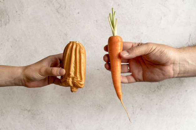 Two people hand comparing healthy and unhealthy food Free Photo