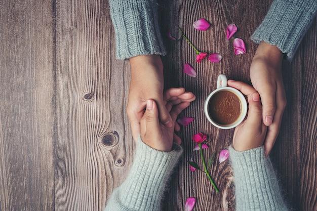 木製のテーブルに愛と暖かさを持って手にコーヒーのカップを保持している2人 無料写真