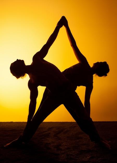 夕日の光の中でヨガを練習する二人 無料写真