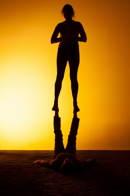 Two people practicing yoga in the sunset light Free Photo