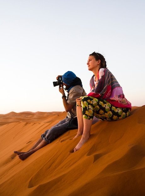 Two people sitting on top of dune taking photos Free Photo