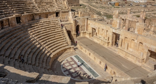 Two people standing in an ancient amphitheater during daytime Free Photo