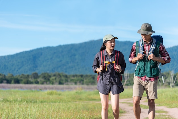 Two people walking on path in meadow. male and female traveler looking at attraction view Premium Photo