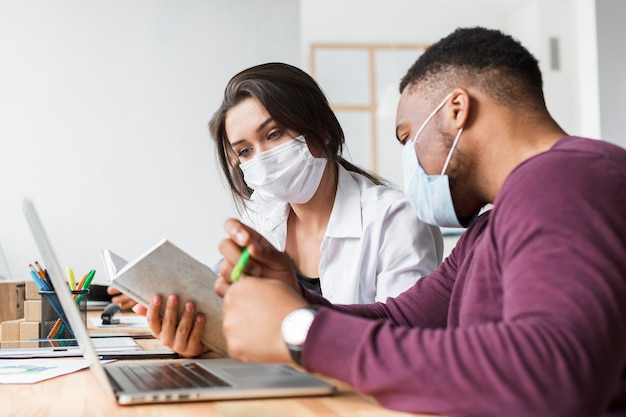 マスクを上にしてパンデミック時にオフィスで一緒に働く2人 Premium写真