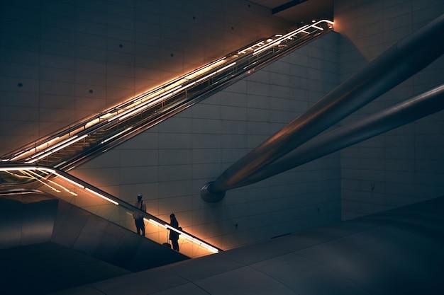 Due persone in piedi sulla scala mobile Foto Gratuite