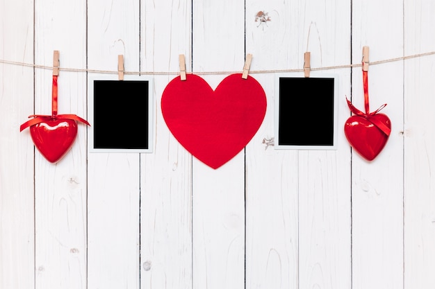 Two photo frame blank and red heart hanging on white wood background ...