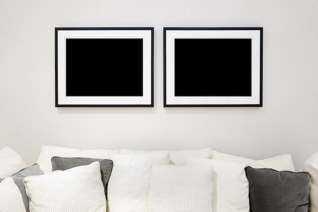 소파와 흰 벽에 포스터 디자인을위한 두 개의 사진 프레임 갤러리 모형 프리미엄 사진