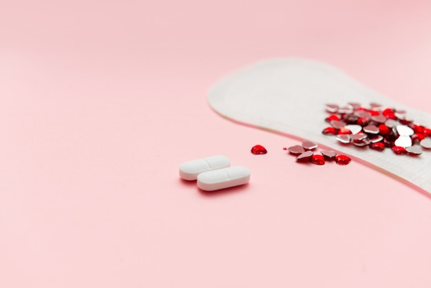 Two pills and menstruation pad with red hearst on it, painkiller contraception concept Premium Photo