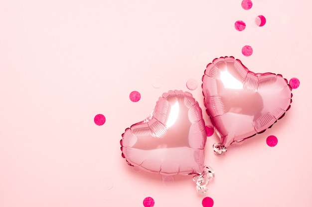 Two pink air balloons in the shape of a heart on a pink background.  valentine's day, wedding decoration. foil balls. flat lay, top view Premium Photo