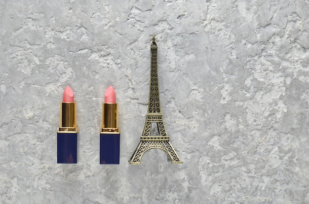Two pink lipsticks and a statuette of the eiffel tower. top view. Premium Photo