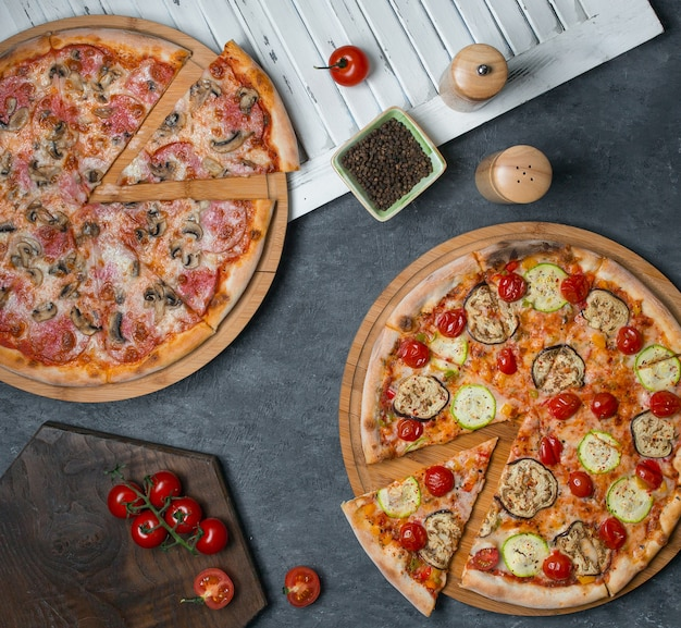Two pizzas with mixed ingredients Free Photo