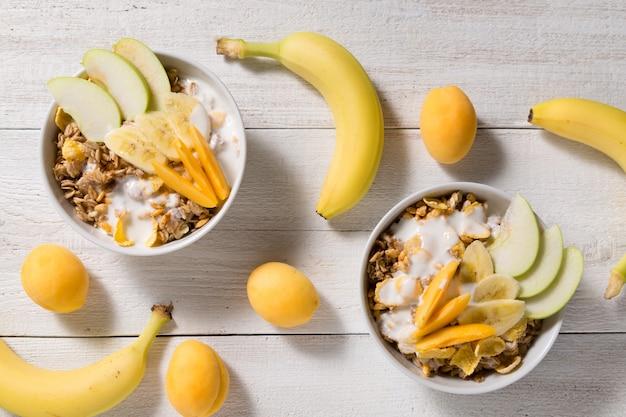 Две тарелки с овсянкой и чашки кукурузных хлопьев и воздушный рис на белом фоне деревянные Premium Фотографии