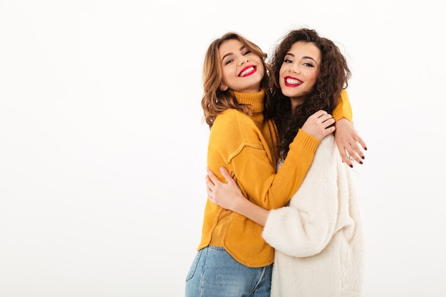 Two pleased girls in sweaters hugging to each other  over white wall Free Photo