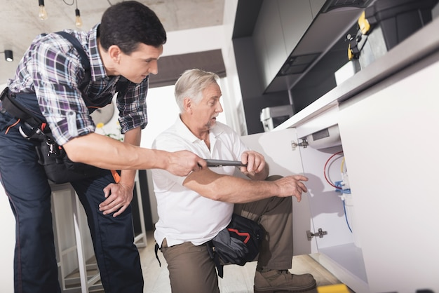 Two plumbers in the kitchen repairing water sink. Premium Photo