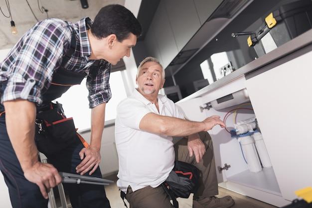 Two plumbers prepared to repair the kitchen sink. Premium Photo