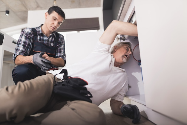 Two plumbers prepared to repair the kitchen sink Premium Photo