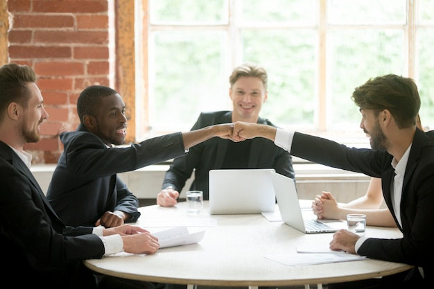 Two positive multiethnic coworkers give each other fist bump. Free Photo