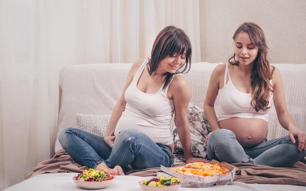 Две беременные женщины едят пиццу и салат дома Бесплатные Фотографии