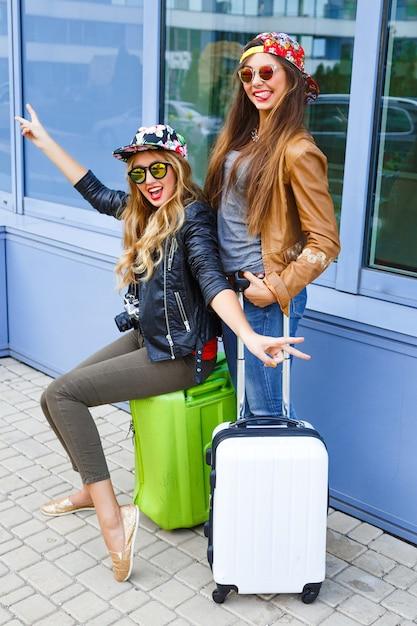 空港の近くで荷物を持ってポーズをとって、旅行に夢中になっている2人のかなり親友の女の子。旅行を楽しんでいる2人の姉妹のライフスタイルの肖像画 無料写真