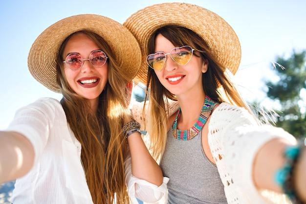 ビーチでセルフィーを作る2人のかなり親友の女の子、明るく明るい夏の色、自由奔放に生きるシックな服の帽子とサングラス、トレンディなジュエリーとナチュラルなメイクアップ、ポジティブな友情の雰囲気。 無料写真