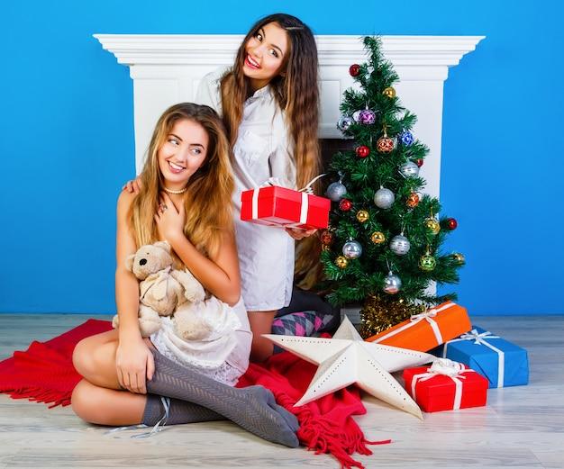 크리스마스를 여는 두 명의 예쁜 가장 친한 친구 소녀는 벽난로 근처에 선물하고 새해 트리를 장식했습니다. 겨울 휴가 시간에 함께 재미. 무료 사진
