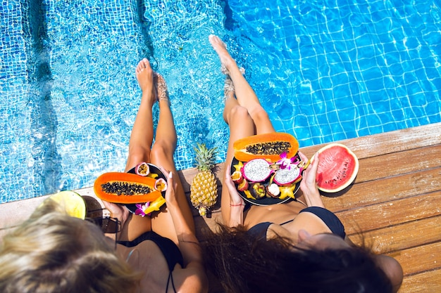 Two pretty blonde and brunette girls having fun and going crazy at tropical fruits party, sexy black bikini, a lot of sweet vegan food, exotic vacation, posing near pool, summer fashion image. Free Photo