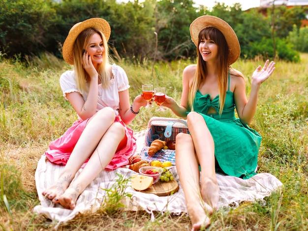 ロマンチックなエレガントなドレスと麦わら帽子を身に着けている2人のかなり陽気な親友の女性 無料写真