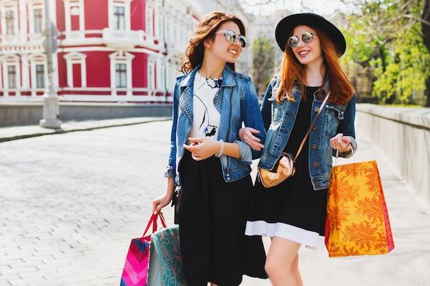 Две довольно веселые женщины делают покупки в городе, гуляют по улицам Бесплатные Фотографии