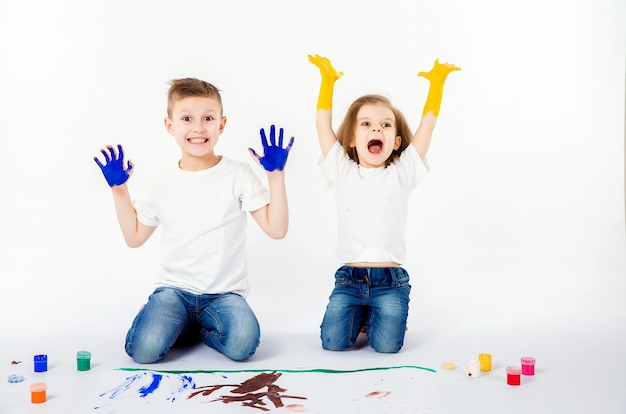Two pretty child friends boy and girl are drawing pictures by paints. showing hands in paint Premium Photo
