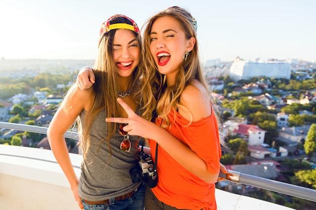 Due belle ragazze alla moda che inviano bacio e si divertono, indossando cappellini e occhiali da sole luminosi Foto Gratuite