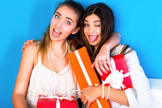 Две красивые подруги девушки держат яркие праздничные подарки Бесплатные Фотографии