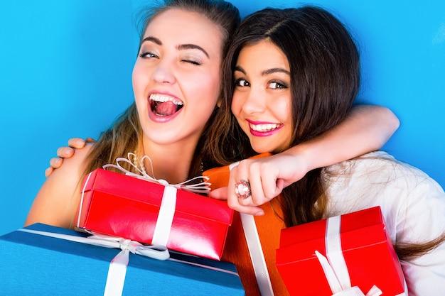 Due ragazze graziose degli amici che tengono i regali luminosi di festa Foto Gratuite