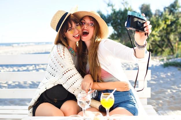 ビンテージカメラでselfieを作る2つのかなり面白い姉妹の女の子、ビーチでポーズ、パーティーや休暇の気分、クレイジーな前向きな気持ち、夏の明るい服のサングラスと帽子。 無料写真