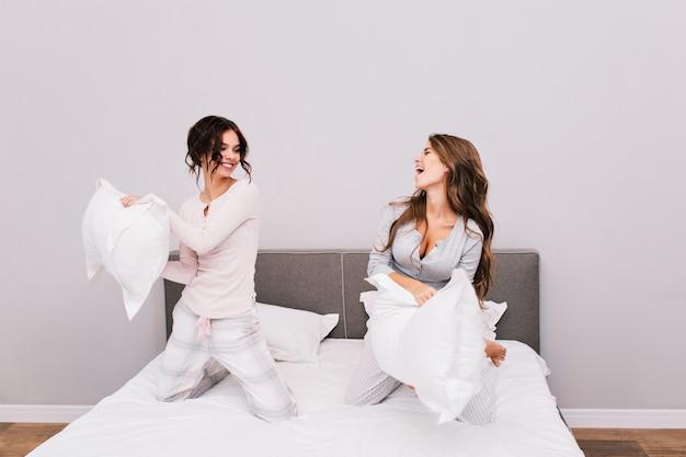 枕を持っているパジャマ姿の2人のかわいい女の子がベッドで戦います。 無料写真