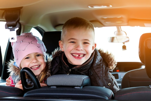 Two pretty little children boy and girl in a car interior Premium Photo