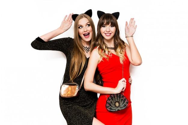 Две красивые женщины в кошачьих карнавальных ушах и вечернем платье веселятся Бесплатные Фотографии