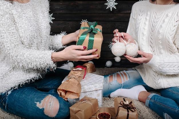 Due belle donne in posa con regali per natale, vista ravvicinata Foto Gratuite