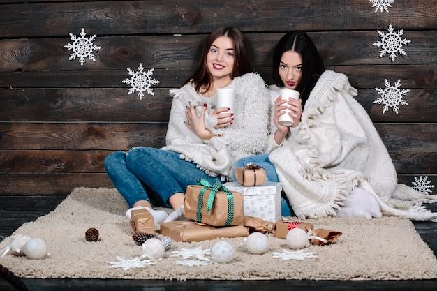 2つのかなり若い面白い女性の友人は笑顔を抱擁し、一緒に寄り添う 無料写真
