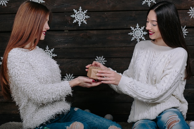 Две симпатичные молодые забавные женщины-друзья улыбаются и веселятся, держа в руках праздничные подарки, готовые к празднованию. Бесплатные Фотографии