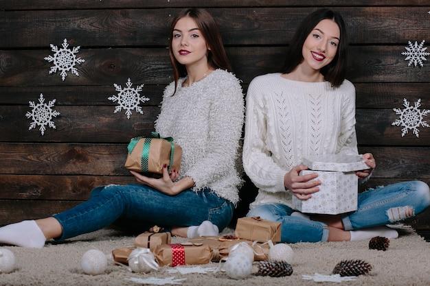 Две симпатичные молодые забавные женщины-друзья улыбаются и веселятся, держа в руках праздничные подарки Бесплатные Фотографии